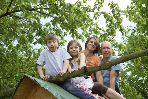 Family with two children sitting on playhouse roof - CUF41321