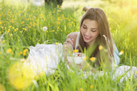Young woman in field of buttercups eating fresh fruit - CUF41360