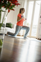 Young woman exercising with dumb-bells at home - CUF41378