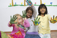 Three girls kneeling on floor with painted hands - CUF41471