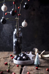 Vhristmas decoration with white and black baubles and twigs with rose hips in a vase - SBDF03625