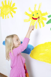 Young girl painting smiling sunshine on wall - CUF41496