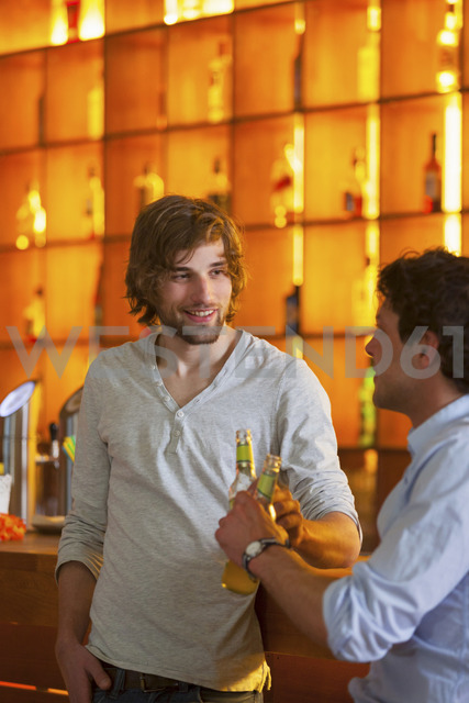 Two men standing at bar with bottles of beer - CUF41502 - Henglein and Steets/Westend61