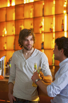 Two men standing at bar with bottles of beer - CUF41502