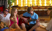 Young man playing guitar to friends in bar - CUF41511