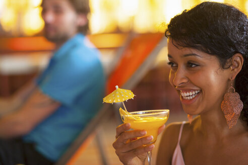 Close up of young woman holding cocktail at indoor beach party - CUF41517