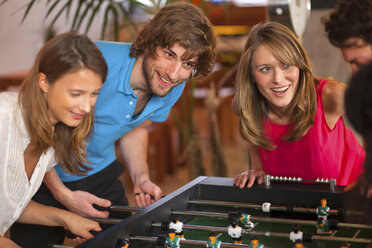Close up of friends having fun playing table football - CUF41523