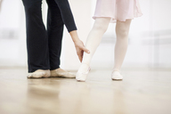 Close up of a young ballerina and teacher practicing toe point - CUF41577