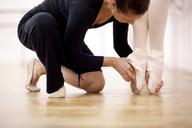 Teacher adjusting foot position of ballerina - CUF41903