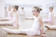 Distracted young ballerina sitting on floor - CUF41918