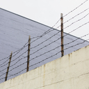 Barbed wire fence at the top of a wall, in a city. - MINF00025