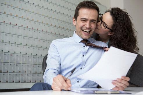 Woman kissing businessman's ear - CUF42008