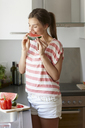 Woman biting slice of watermelon - CUF42077