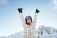 Portrait of teenage girl skier with arms raised, Les Arcs, Haute-Savoie, France - CUF42173