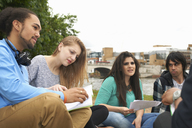 College students sitting outdoors with papers - CUF42224