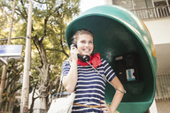Young woman using pay telephone - CUF42284