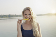 Portrait of young woman biting ice lolly - CUF42344