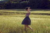 Young woman walking through meadow - CUF42356