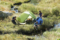Three people camping by stream, Chamonix, Haute Savoie, France - CUF42377