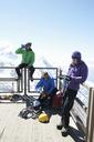 Three climbers resting by fence, Chamonix, France - CUF42398