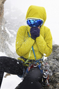 Mid adult woman wearing yellow jacket and ski goggles in snow - CUF42404
