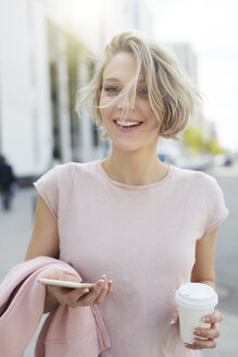 Portrait of happy blond woman with takeaway coffee and cell phone in the city - PNEF00718
