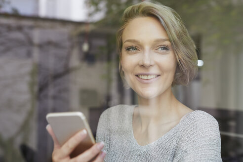 Portrait of smiling young woman with cell phone behind windowpane - PNEF00730
