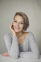 Portrait of smiling blond woman wearing grey pullover - PNEF00733