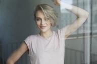 Portrait of smiling blond woman behing windowpane - PNEF00739