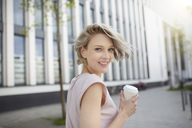 Portrait of happy blond woman with takeaway coffee in the city - PNEF00745