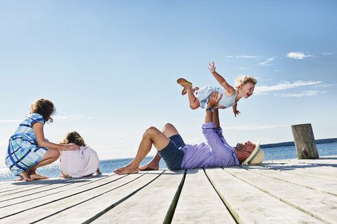 Family playing on jetty, Utvalnas, Gavle, Sweden - CUF42670