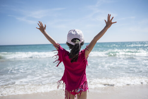 Little girl standing at the beach with raised arms, having fun, rear view - JASF01891