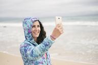Woman taking smartphone selfie at the beach, wearing windbreaker - JASF01894