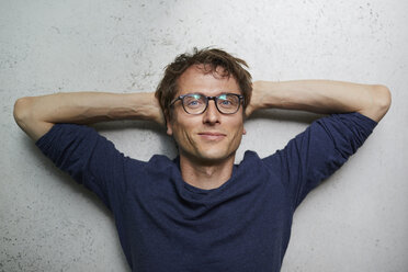 Portrait of smiling man with hands behind head wearing glasses - PNEF00751