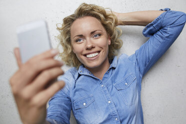 Portrait of smiling blond woman taking selfie with smartphone - PNEF00754
