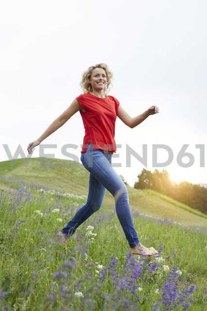 Portrait of happy blond woman running barefoot on a meadow - PNEF00760
