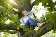 Smiling blond woman relaxing in nature - PNEF00766