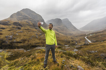 UK, Scotland, man in the Scottish highlands near Glencoe with a view on the Three Sisters taking a selfie - WPEF00682