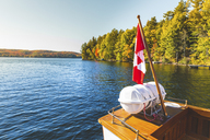 Canada, Ontario, Canadian flag on a boat on a lake in Algonquin park - WPEF00709