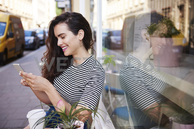 Happy young woman using cell phone at outdoor cafe in the city - ABIF00685