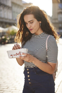 Smiling young woman eating strawberries in the city - ABIF00688