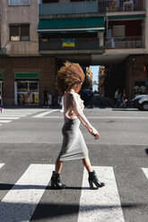 Young woman with afro hairdo crossing the street in the city - MAUF01488