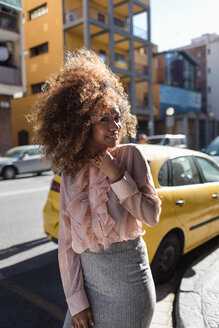 Portrait of smiling beautiful young woman with afro hairdo in the city - MAUF01491