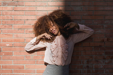 Portrait of beautiful young woman with afro hairdo at brick wall in sunshine - MAUF01494