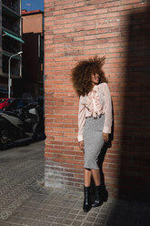 Smiling young woman with afro hairdo standing at brick wall in the city - MAUF01497