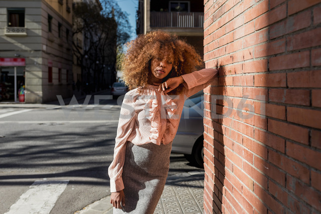 Portrait of beautiful young woman with afro hairdo leaning against brick wall in the city - MAUF01500