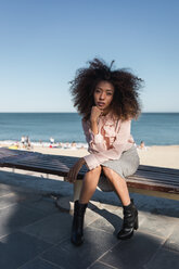 Portrait of beautiful young woman with afro hairdo sitting on a bench at the beach - MAUF01503