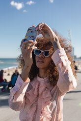 Stylish young woman taking a selfie at seaside promenade - MAUF01506
