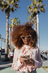 Stylish young woman using cell phone at seaside promenade - MAUF01509