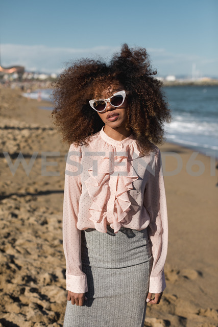 Portrait of beautiful young woman with afro hairdo standing on the beach - MAUF01512